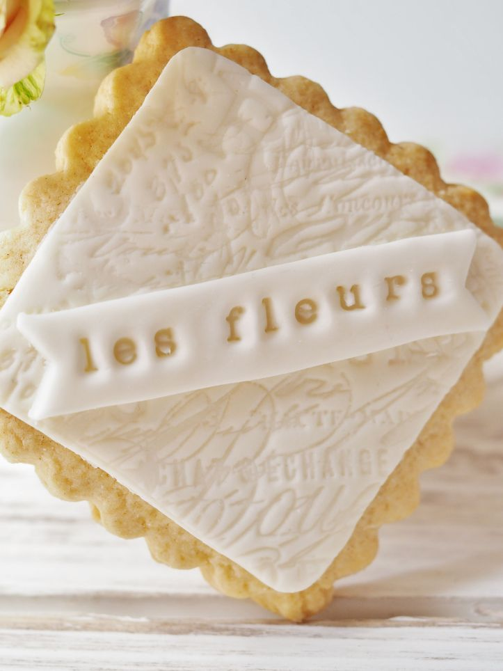 Hand baked square scalloped edged biscuit with the words 'Les Fleurs' stamped on white fancy icing