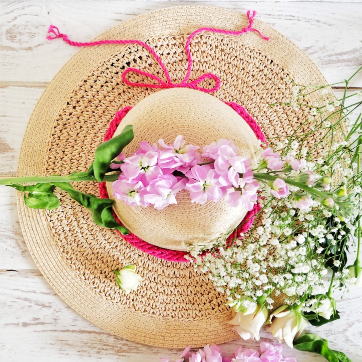 Panama straw hat on white wood floorboards. Laden with lilac flowers and decorated with a hand knitted hat band. Link to the Hat Band and Head Band section of the One Purl Row Etsy store.