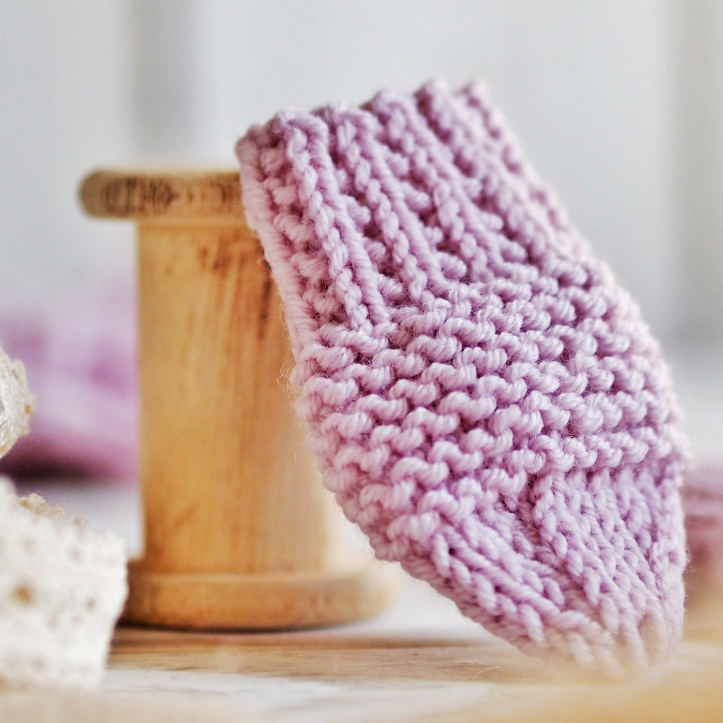 Pastel lilac hand knitted baby mitten leaning against vintage cotton reel. Link to the One Purl Row Etsy store.