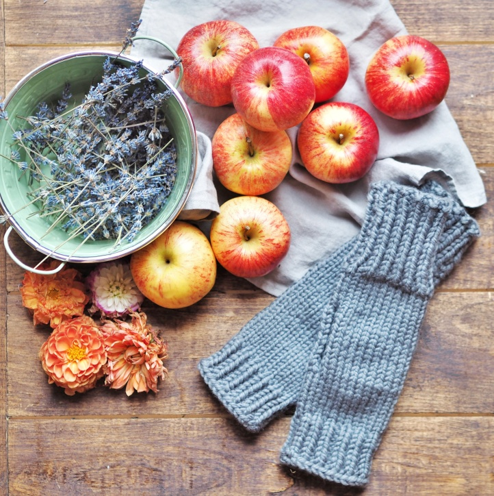 Grey kniitted fingerless mittens with Autumn fruit and flowers and tins of dried lavender on a dark wood and grey linen background.  Link to purchase mittens on Etsy store.
