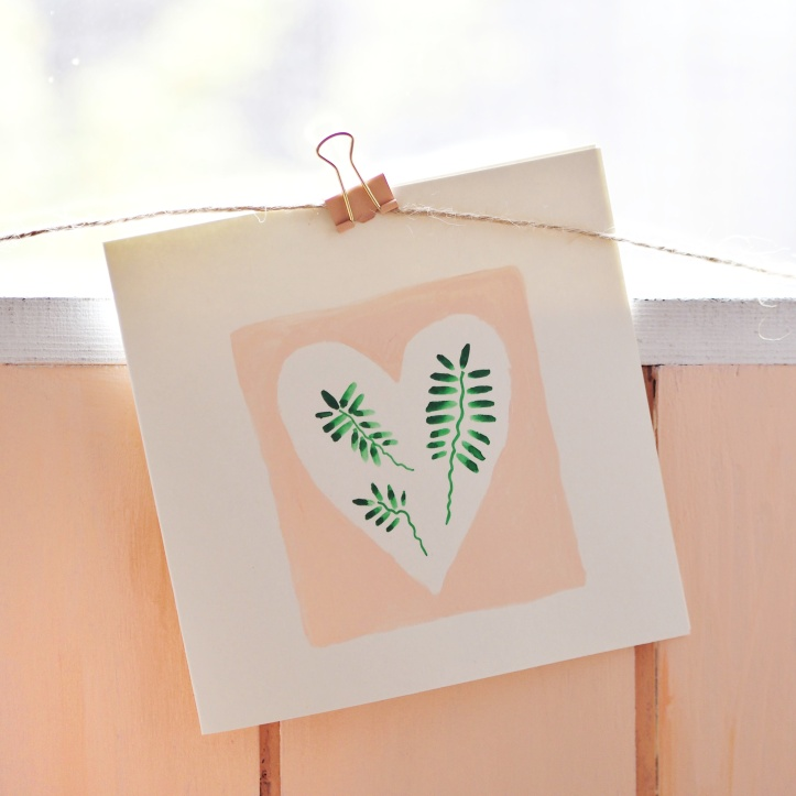 Hand painted leaves on coral background blank greetings card or notecard.   Hanging on rustic twine against coral wooden fence. Link to One Purl Row Etsy store e