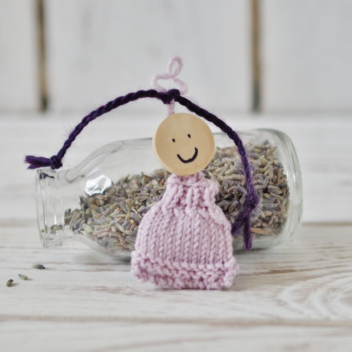 Cute mini lavender doll in pastel lilac with super cute plaits and a wooden bead with face drawn on. Leaning against a mini milk bottle of dried lavender against a backdrop of white wooden floorboards . Link to the One Purl Row gift section in the Etsy shop