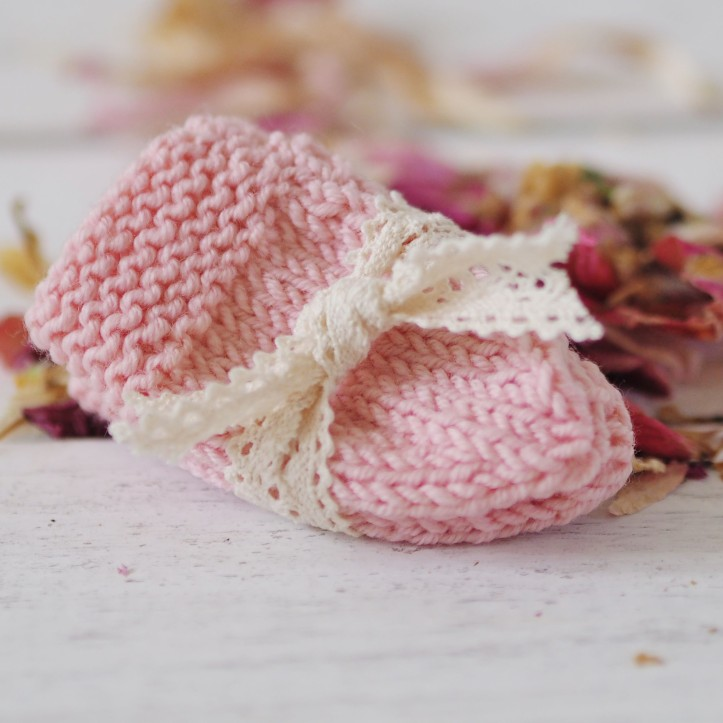 Hand knitted pastel pink baby mittens wrapped in vintage lace on a backdrop of white wooden floorboards and pink rose petals. Link to the One Purl Row Knitting Patterns section in the One Purl Row Etsy store