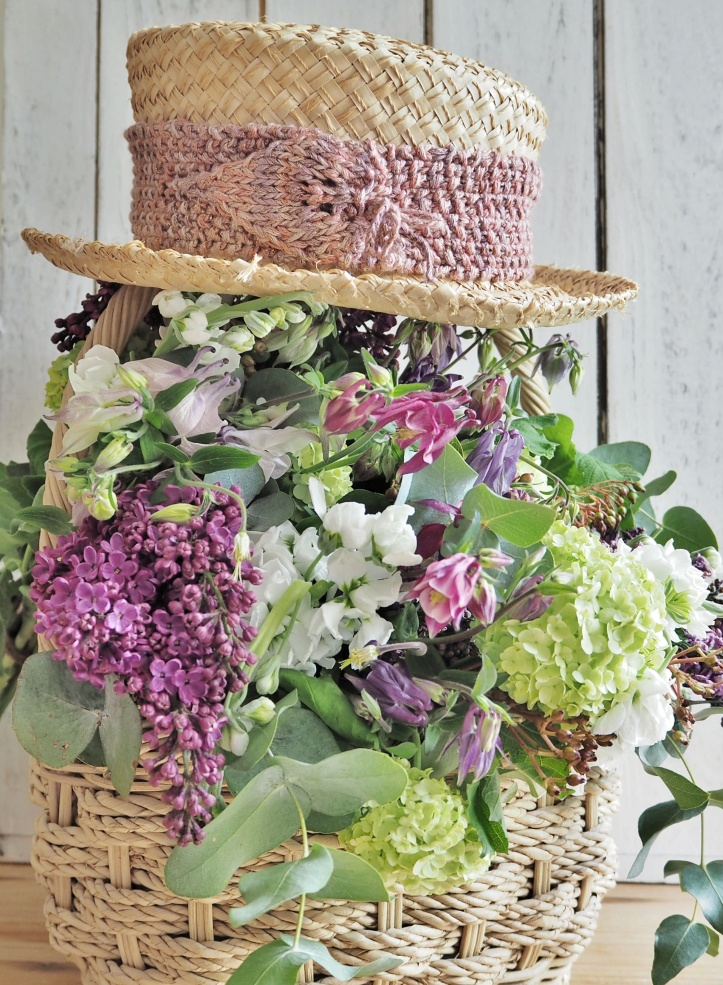 Hand knitted hat band on straw hat on top of basket of flowers. Example of styled product photography