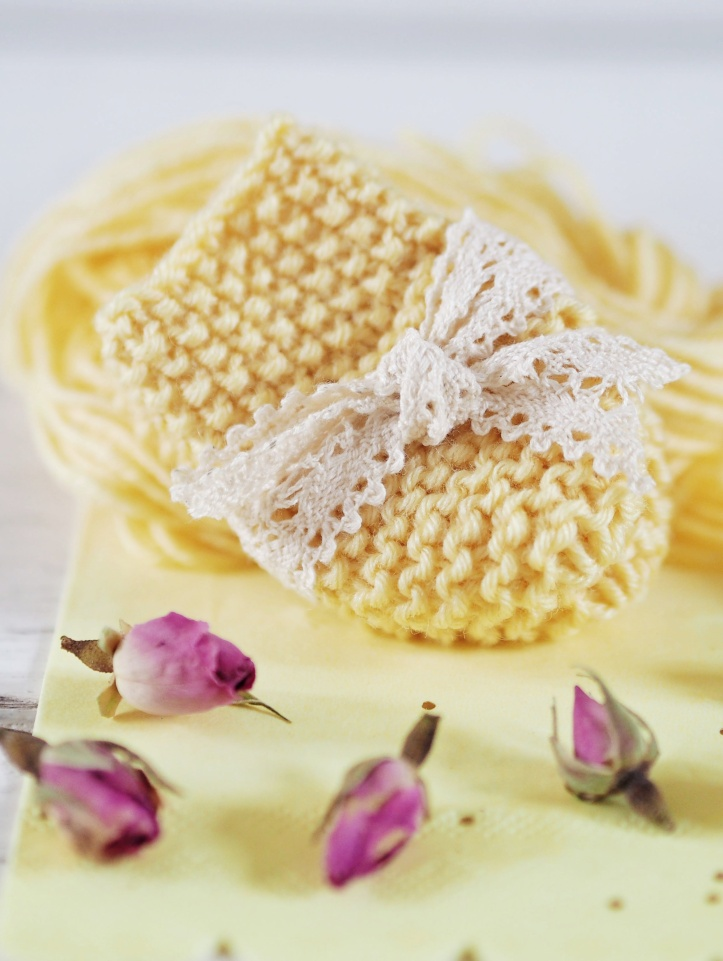 Lemon hand knitted baby mittens tied with cream lace. Example of styled product photography