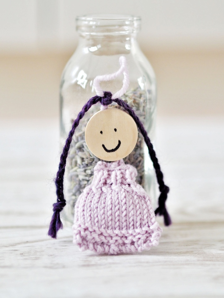 Hand knitted lavender doll in lilac with purple braids. Leaning on mini milk bottle filled with dried lavender. Example of styled product photography