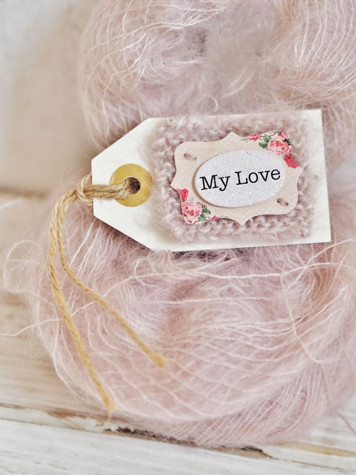 My Love gift tag appliqued on vintage pink mohair silk hand knitted square and tied with twine. On background of pink mohair silk yarn. Example of product photography.