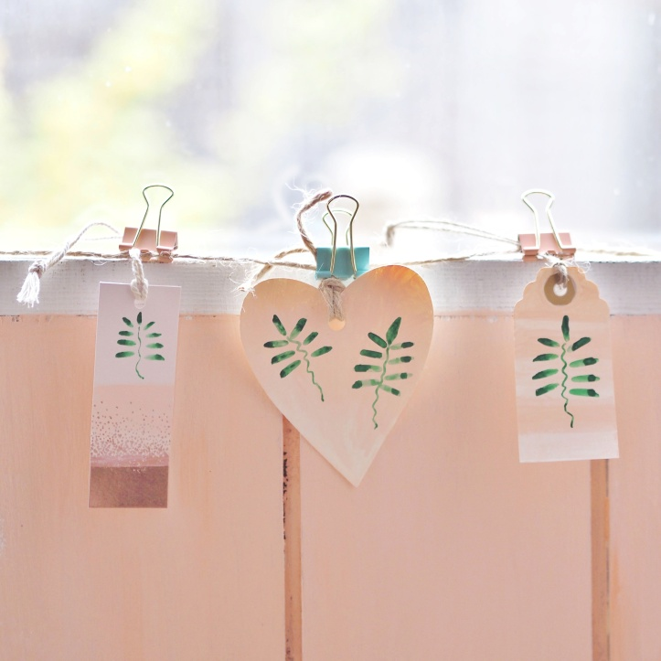 Hand painted different shaped gift tags with green leaves on coral background. Hanging on twine against a coral fence with the sunlight bleaching out the background. Example of styled product photography.