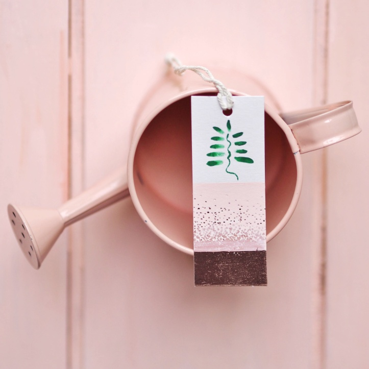 Gift tag with hand painted leaves on rose gold and coral background. Balance on coral watering can and coral rustic floorboards. Example of styled product photography