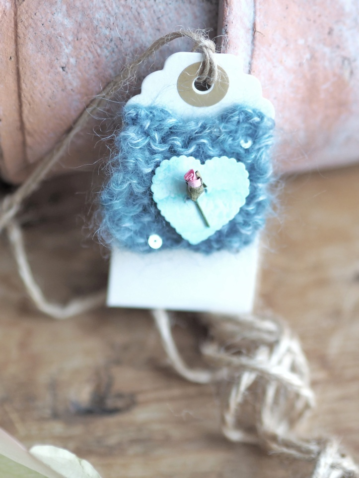 Cream gift tag tied with rustic twine. Appliqued with mohair silk knitted square, turquoise heart and tiny single rose. Example of styled product photography