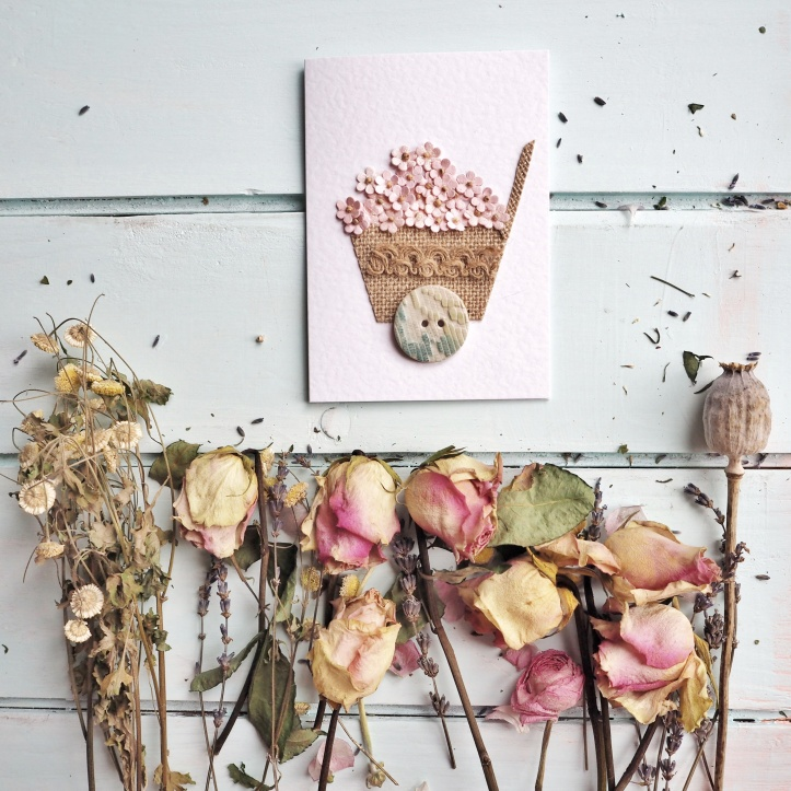 White hammered card appliqued with wheelbarrow of pink flowers. Set on background of pastel aqua floorboards with pink dried roses. Example of product photography