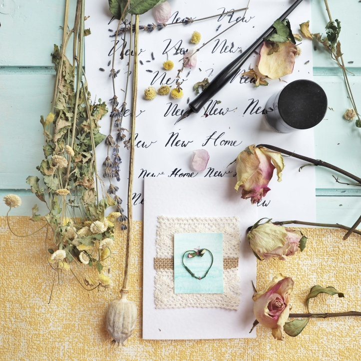 White hammered card appliqued with cream lace and heart shaped wreath on turquoise background. Scene of calligraphy writing, pen and ink on floor boards with dried flowers. Example of product photography.